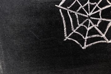 White chalk hand drawing in spiderweb shape on blackboard background