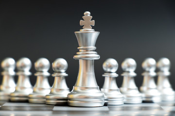 Silver king chess piece stand in front of pawn on black background (Concept of leadership, management)