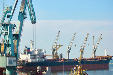 Ship with cranes. Marine Industrial Commercial Port. Warm sunny day with clear sky.