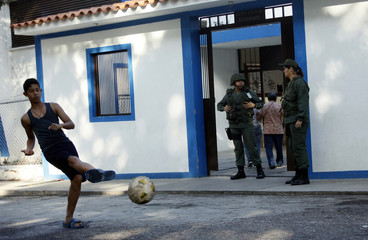 A youth kicks a ball in front of a polling station during the presidential election in San Cristobal