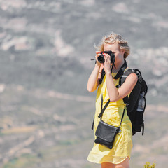 Female traveler with a backpack on her back enjoying the views from the mountains of Montserrat in Spain and makes a photo on her camera. The girl in a yellow dress on background of the nature