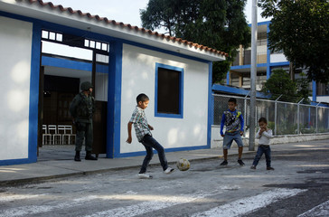 A youth kick a ball in front of a polling station during the presidential election in San Cristobal