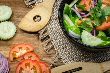 Salad in black bowl on wooden table with tablecloth