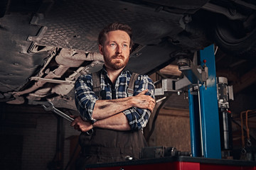 Mechanic crossed hands while standing under lifting car in a repair garage.