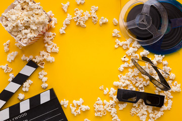 Clapperboard, 3D glasses and popcorn on yellow background