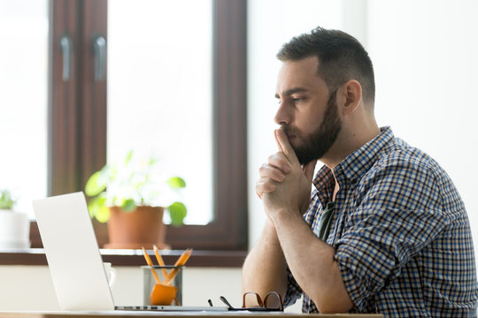 Concerned millennial male worker looking at laptop screen thinking about problem solution, startup project strategies, company business success or profit increase. Businessman reading online news