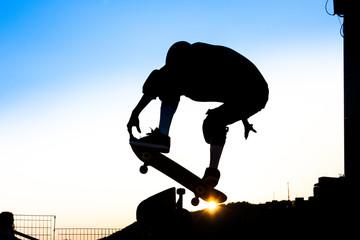 Boy practicing skateboard at sunset.