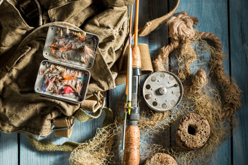 Fishing tackle with fishing flies and rods on wooden table