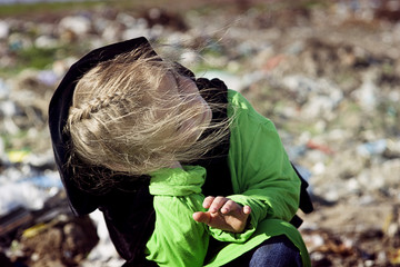 A homeless girl in a garbage dump with sadness looks up at the sky