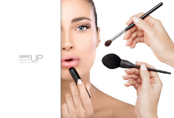 Beautiful model girl in make up process with makeup brushes