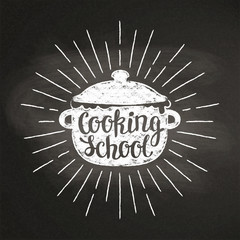 Boiling pot chalk silhoutte with sun rays and lettering - Cooking school - on blackboard. Good for cooking logotypes, bades or posters.