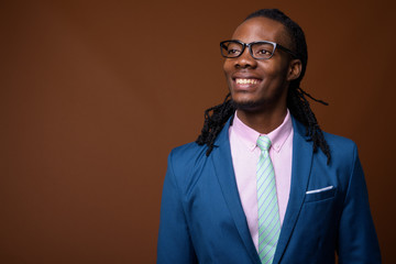 Young handsome African businessman wearing eyeglasses against br