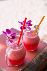 Watermelon Smoothie in glass with watermelon and flower on wooden background