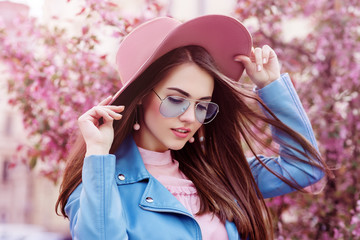 Young beautiful fashionable girl wearing stylish blue color aviator sunglasses, pink suede hat, earrings, biker jacket. Model posing in street with flowering trees. Spring fashion concept.