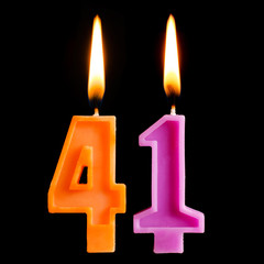 Burning birthday candles in the form of 41 forty one for cake isolated on black background.