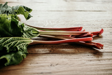 Bundle of red rhubarb stalks with large green leaves freshly harvested from the garden or bought on farmer market. Wooden background, copy space, horizontal.