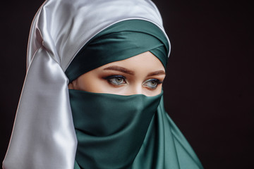 close up side view shot. a pretty lady is dressed in green hijab. fashion moslem with pensive look