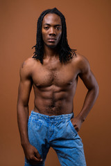 Young handsome African man shirtless against brown background