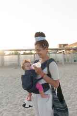 a small child sits in a backpack and walks along with the mother along the seashore. Summer family vacation concept