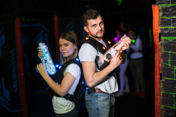 Two laser tag players standing back to back