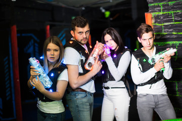 Young people with laser guns on lasertag arena