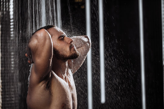 relaxing time.fresh shower concept.under good looking man is under water drops