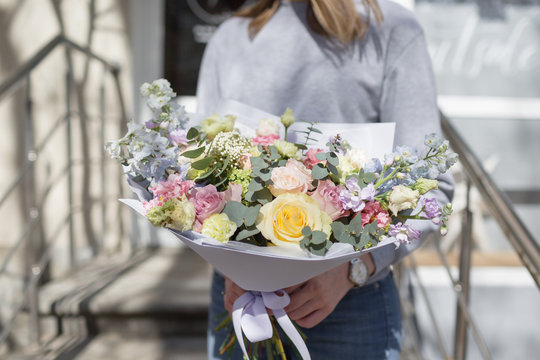 bouquet of beautiful flowers in women's hands. Floristry concept. Spring colors. the work of the florist at a flower shop