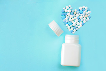 Medicine pills, tablets and capsules for the treatment of heart disease. Heart shape and bottle of pills. Blue background. Copy space for text