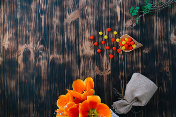 Tulips with sweets in a waffle horn on a wooden background
