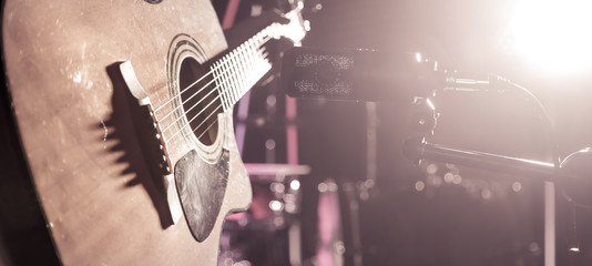 The Studio microphone records an acoustic guitar close-up. Beautiful blurred background of colored lanterns.