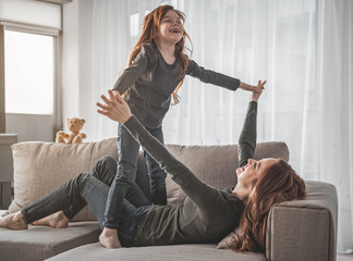 I believe I can fly. Full length portrait of small smiling girl and her amused mother are lying on sofa with their fingers crossed while entertaining. Cheerful child pretending being bird