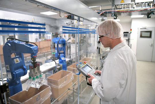 Arbeiter in der Pharamindustrie steuert Industrieroboter in moderner Fertigungsanlage zur Herstellung von Infusionsbeuteln // Workers in the pharmaceutical industry - production infusion bags