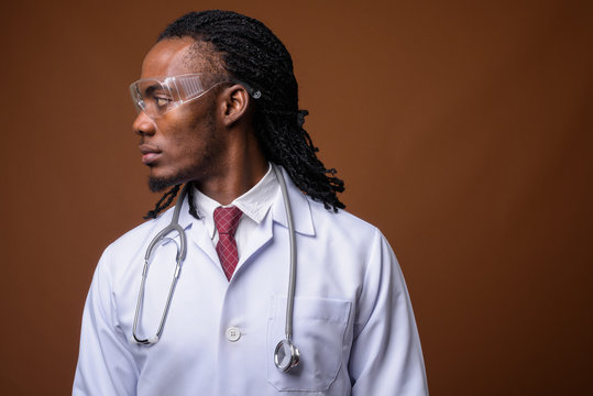 Young handsome African man doctor wearing protective glasses aga