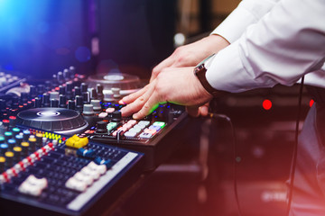 closeup hands of DJ at the professional console wearing white shirt. disc jockey playing on the best, famous CD records at night club. EDM, party clubbing life concept