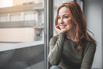 Portrait of red-haired happy woman resting at home. She is smiling while looking through window with pleasant expectation. Copy space in left side