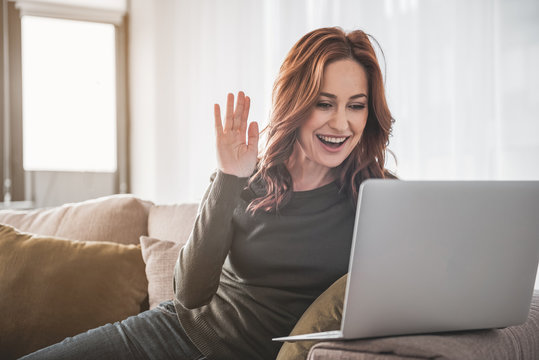 Hello. Waist up portrait of cheerful girl sitting on her couch at home. She is waving hand with smile at her laptop