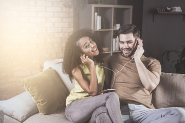 Sharing our good mood. Portrait of cheerful young couple in love is listening to music while resting at home. They are wearing earphones and using player on phone. Girl is looking at camera with joy