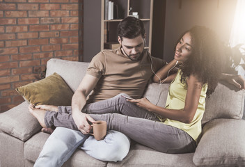 Our song. Top view of young relaxed couple is sitting on cozy sofa at home. They are enjoying playlist on modern smartphone and listening to music using earphones. Man is holding cup of coffee
