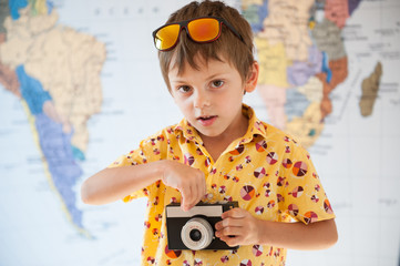 handsome boy in vivid yellow shirt with film retro camera in hands on world map background