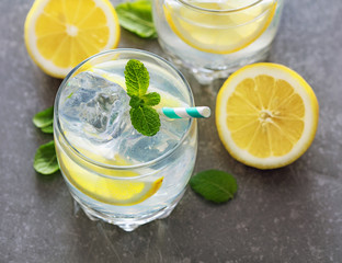 top view of two glasses of lemonade with lemons and mint on gray background