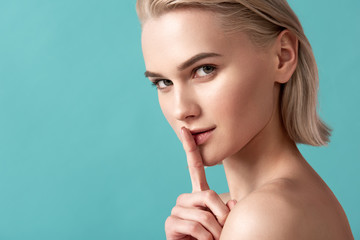 Quietness concept. Portrait of groomed blonde girl looking at camera and holding her index finger on lips. Copy space in left side. Isolated on blue background Wall mural