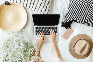 Young woman typing on laptop in bed. Lifestyle hero header with view from above with white flowers bouquet, pillow, hat, cell phone and wooden plate. Freelancer or fashion blogger home workspace