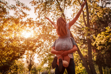 Happy couple having fun in blooming garden. Man holds his girlfriend in hands and spins at sunset. Guys enjoying life