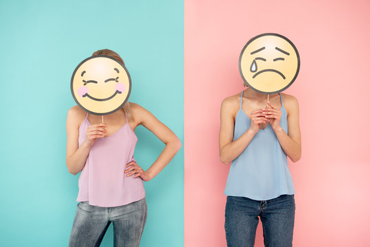 Emoji atmosphere. Waist up of smiling girl and her crying female friend posing on blue and pink background