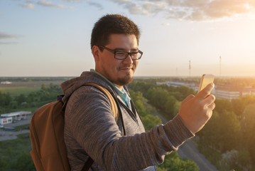 Young beard man in glasses doing selfie on the phone  on park background.