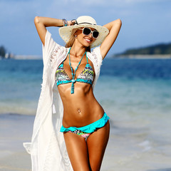 Beautiful girl with a tanned body enjoying freedom on the beach