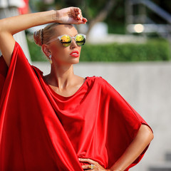 Fashion portrait of blonde girl in red dress and sunglasses