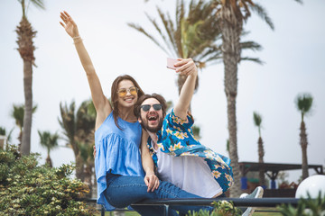 We are free. Portrait of cheerful young loving couple photographing themselves on cellphone in the nature. Girl is raising hand up while guy is holding smartphone
