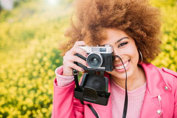 Happy mixed race woman in a beautiful flower field holding a vintage camera