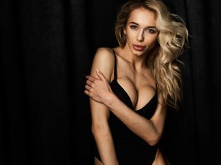 Beautiful blonde girl with long legs in black bodysuit against black velvet curtains in white sneakers.